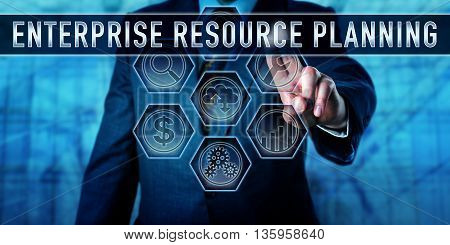 Male corporate manager is touching ENTERPRISE RESOURCE PLANNING on an interactive virtual control monitor. Business management metaphor and information technology concept for ERP. Business term.
