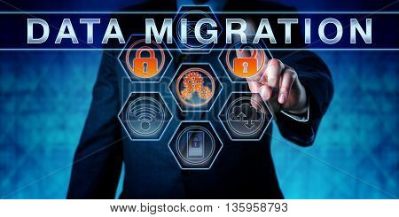 Male corporate manager pushing DATA MIGRATION on an interactive virtual control monitor. Business challenge metaphor and data management concept for a secure transfer process of data across systems.