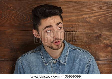 Young model man in jeans shirt demonstrating his modern hairstyle in studio. Handsome male posing over wooden background.