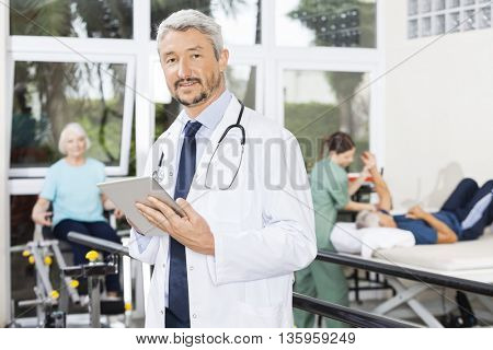 Male Physiotherapist Using Digital Tablet At Fitness Center