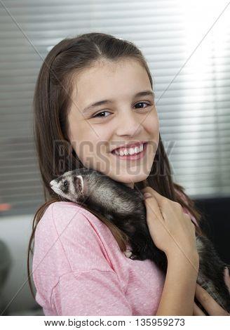 Happy Girl Holding Weasel In Veterinary