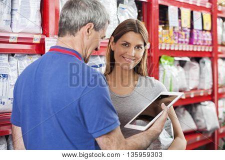 Customer Standing By Salesman Using Digital Tablet In Pet Store