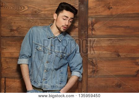 Portrait of model man posing for fashionor vogue magazine over wooden background. Handsome male with modern hairstyle keeping handsin pockets in studio.