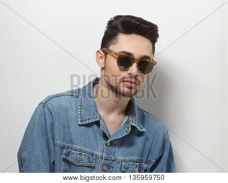 Handsome man in jeans shirt wearing sunglasses while posing for photographer in studio. Male with modern hairstyle over white background.