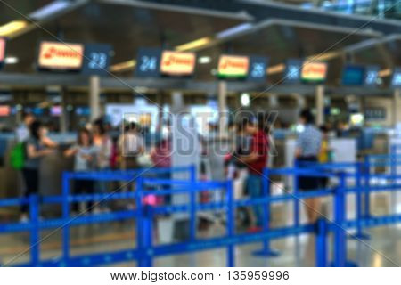 tourists at airport check-in counter / ticket counter - blurred