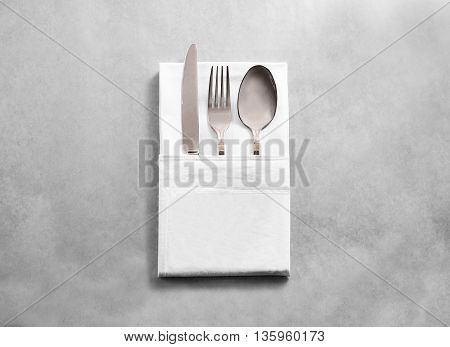 Blank white restaurant cloth napkin mockup with silver cutlery set, isolated. Knife fork and spoon in clear textile towel mock up template. Cafe branding identity clean napkin surface for logo design.