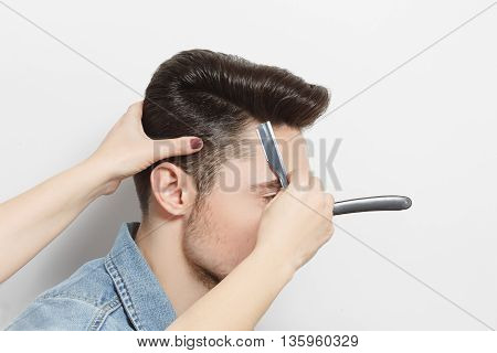 Hairdresser cutting black hair of handsome man with blade. Modern hairdressing technologies. Studio shot. White background.