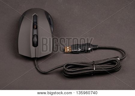 Black computer optical mouse isolated on black background with soft shadow