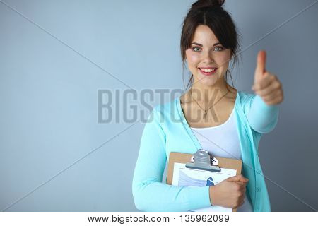 Young brunette showing big thumbs up on white background.