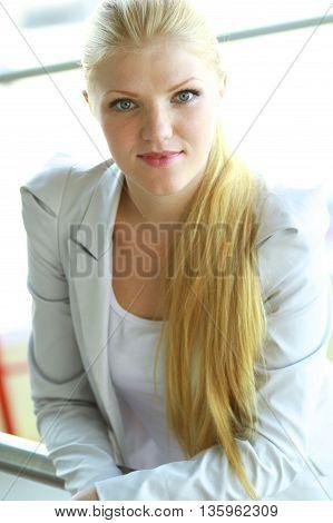 Business woman in modern building , standing near windows.