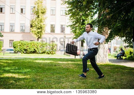 Business man runs in the park outdoors. Late for work.