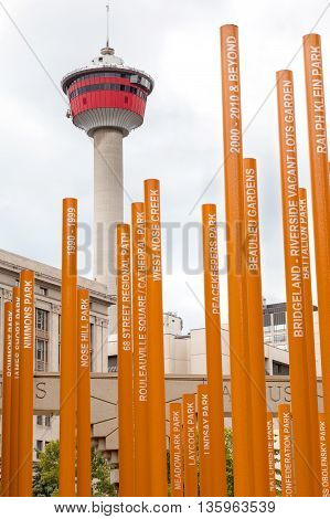CALGARY, CANADA - JUNE 18: The Centennial Grove at Olympic Plaza with the Calgary Tower in the background June 18, 2016. The grove was installed to celebrate Calgary Parks' 100 Anniversary. Each orange tree has a name of a public park inscribed on it.