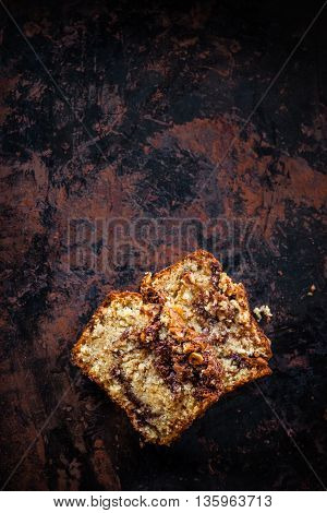 Top view of two pieces of banana bread with nutella swirl and chopped hazelnuts on dark background. Dark food photography. Free text space.
