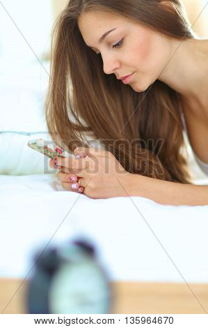 Shot of a beautiful young woman reading a text message while lying on her bed.