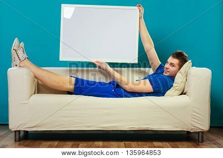 Man On Sofa Holding Blank Presentation Board