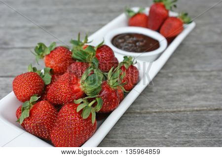 Fresh strawberries on a white platter with chocolate dipping sauce, on a wooden outdoor table. Photographed with shallow depth of field.