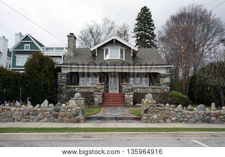 HARBOR SPRINGS, MICHIGAN / UNITED STATES - DECEMBER 24, 2015: An elegant stone wall stands in front of a charming house made of stone and brick, across from the Zorn Park Beach in Harbor Springs.