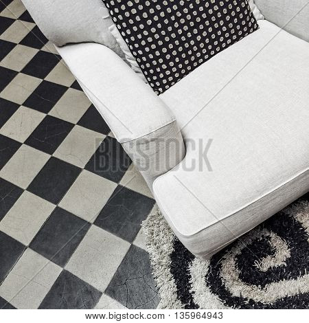 Black and white home interior with stylish armchair and tiled floor.