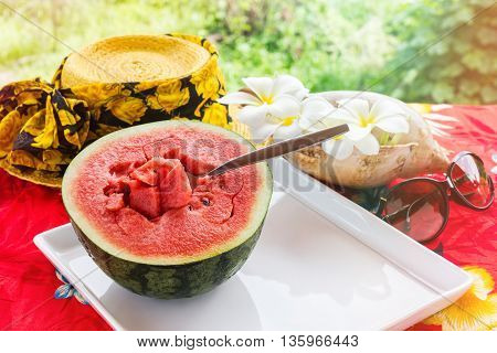 Half fresh and red watermelon fruit and spoon on white tray on table with yellow summer hat and plumeria or frangipani flowers with sea conch shell in background watermelon in sunny day with mood of relaxing in summer vacation