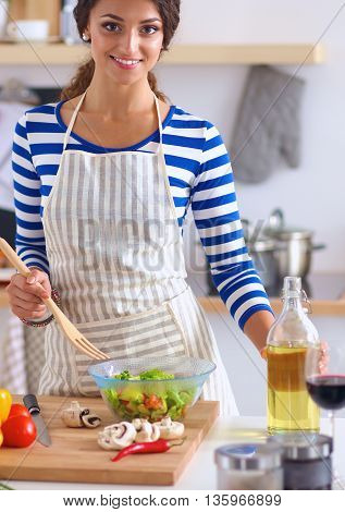Young woman mixing fresh salad, standing near desk .