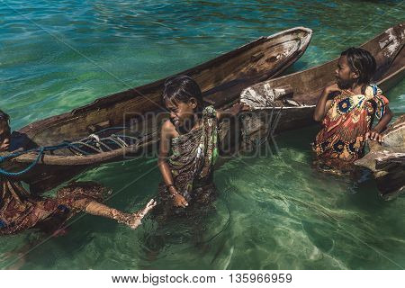 Denawan Island Sabah Malaysia - April 30 2016 : Shot of a group of people in batik traditional clothing pulling their wooden boats to start their day.