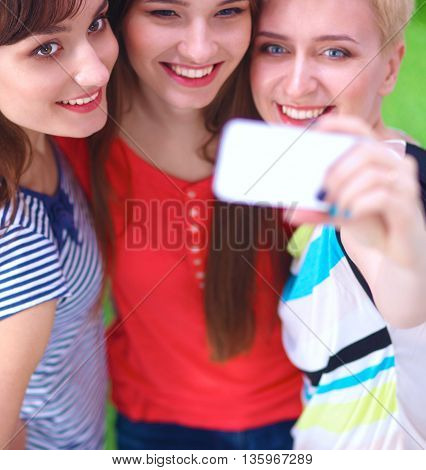 Female friends taking selfie with mobile phone .