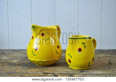 French Country Style Pretty Yellow Milk Jugs on Rustic Wooden Board