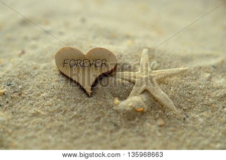 Depth of field forever text carved/engraved in heart shape piece of wood on sand beach with starfish