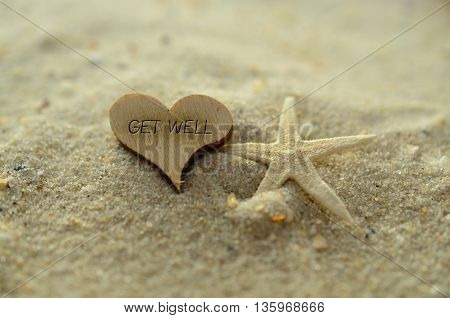 Depth of field get well text carved/engraved in heart shape piece of wood on sand beach with starfish