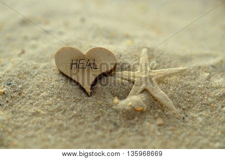 Depth of field heal text carved/engraved in heart shape piece of wood on sand beach with starfish