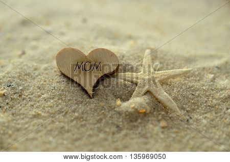 Depth of field mom text carved/engraved in heart shape piece of wood on sand beach with starfish