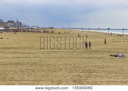 The Hague The Netherlands - June 17 2016: The beach and Sea in the area of Scheveningen in The Hague The Netherlands with silhouettes of factories and smoke in the background.