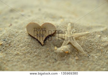 Depth of field thank you text carved/engraved in heart shape piece of wood on sand beach with starfish