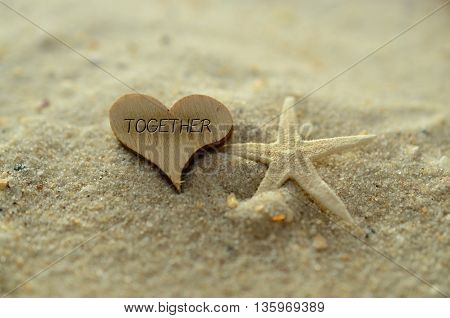 Depth of field together text carved/engraved in heart shape piece of wood on sand beach with starfish