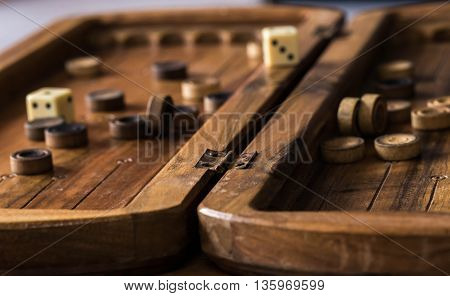 wooden Board with backgammon, pawns with dice, close up