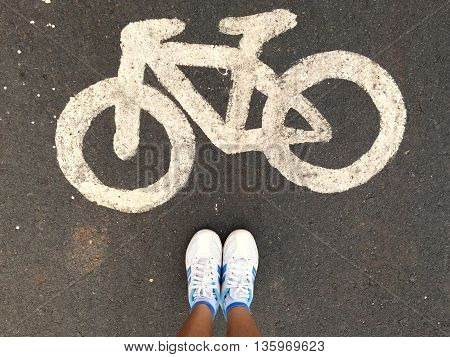 woman wearing sneakers shoes with bicycle sign on street