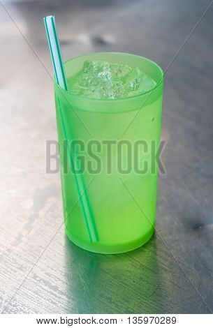 green drinking straw in a green plastic grass of ice water in a street restaurant.
