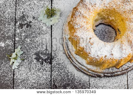 Top View on Marble Bundt Cake with Sugar and Flower on a Dark Wood Table