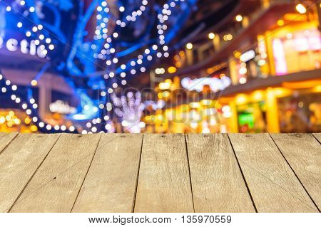 Empty wooden table or plank with bokeh of light from night market on background for product display.