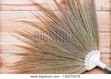 close up straw broom on wooden background