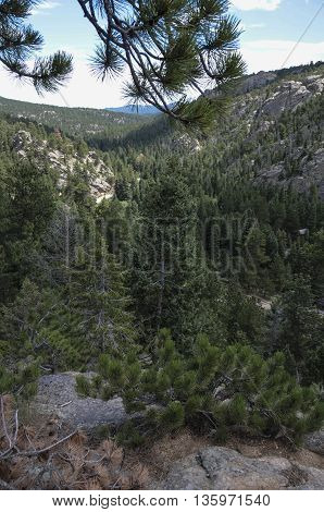 A view down into a valley from atop a mountain.