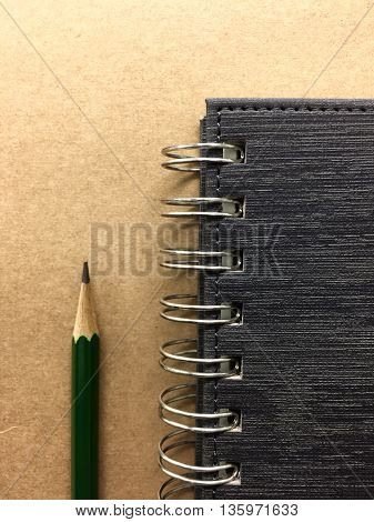 Pencil and book on brown wooden background