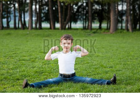 little boy sitting on the splits in the park
