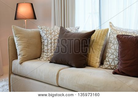 Sturdy Brown Tweed Sofa With Brown Patterned Pillows And Lamp