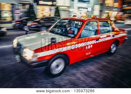 Tokyo Japan - February 27 2015: Man drives typical Toyota cab on the street of Ginza district in Tokyo