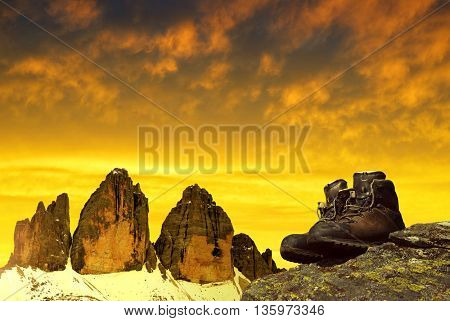 Hiking shoes on the rock in the background Tre Cime di Lavaredo at sunset - Dolomites, Italy