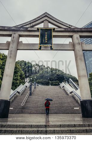 Tokyo Japan - February 26 2015: Man with umbrella passes under Sanno torii gate of Shinto Hie Shrine in Tokyo