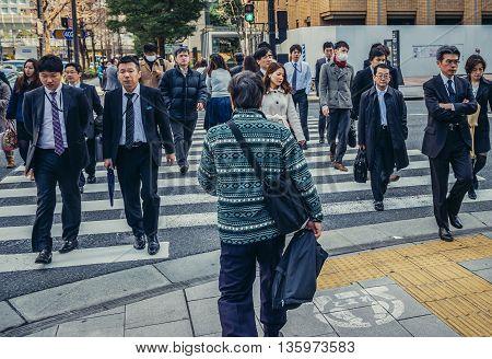 Tokyo Japan - February 27 2015: Pedestrians passes pedestrian crossing in Marunouchi dsitrict in Tokyo