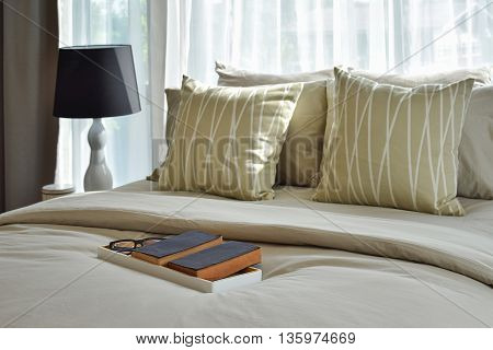 Decorative Wooden Tray With Books And Striped Pillows In Stylish Bedroom Interior