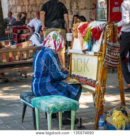 Istanbul Turkey - Aug 26 2013: woman weaver makes traditional Turkish carpet on the streets of Istanbul. Carpets is one of traditional souvenirs in Turkey